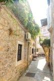 导致鱼餐馆的狭窄的街道在老布德瓦,黑山 免版税图库摄影