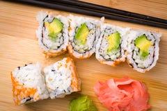 寿司加利福尼亚滚动开胃菜用与筷子的米鲕梨 免版税库存照片