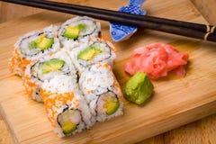 寿司加利福尼亚滚动开胃菜用与chopstic的米鲕梨 免版税库存图片