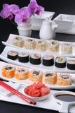 寿司卷健康食物-日本式 各种各样的种类在白色板材服务以兰花为背景 库存照片
