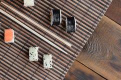 寿司卷和木筷子在一张竹秸杆serwing的席子说谎 亚洲食物炒饭传统蔬菜 顶视图 库存图片