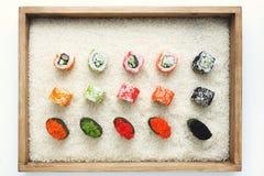 寿司卷和gunkan在米的木制框架 免版税库存照片