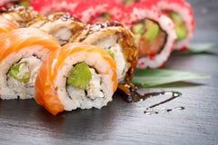 寿司卷特写镜头 日本食物在餐馆 加利福尼亚寿司卷设置了用三文鱼、鳗鱼、菜和飞鱼鱼子酱 库存照片