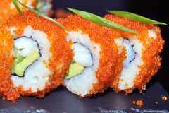 寿司卷特写镜头 日本食物在餐馆 加利福尼亚寿司卷设置了用三文鱼、鳗鱼、菜和飞鱼鱼子酱 免版税库存图片