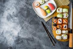 寿司卷用虾、棍子和刀子在黑暗的背景 背景概念藏品查出海螯虾柠檬海鲜白色 平的位置 顶视图 图库摄影