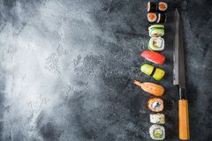 寿司卷用虾和刀子在黑暗的背景 食物框架 平的位置 顶视图 库存照片