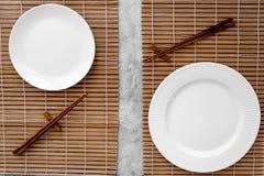 寿司卷的表设置 在席子的空的板材在灰色台式视图大模型的筷子附近 库存照片