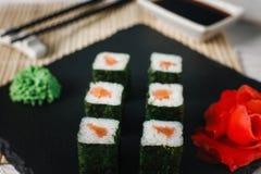 寿司卷设置与三文鱼在黑板岩服务 免版税库存照片
