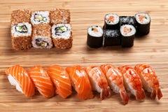 寿司卷设置了与金枪鱼和熏制的鳗鱼和芝麻在木背景 免版税图库摄影