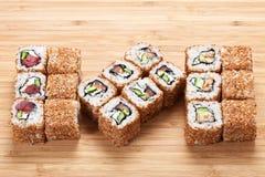 寿司卷设置了与金枪鱼和熏制的鳗鱼在木背景 库存图片
