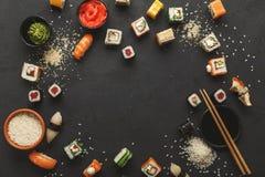 寿司和卷背景,在黑,顶视图的框架 免版税库存图片