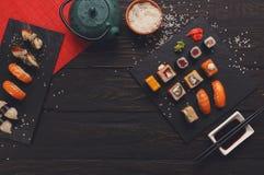 寿司和卷背景,在黑,顶视图的框架 库存图片