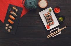寿司和卷背景,在黑,顶视图的框架 库存照片