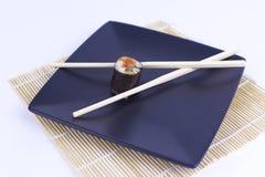 寿司和筷子特写镜头在一个黑色的盘子 库存照片
