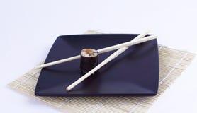 寿司和筷子特写镜头在一个黑色的盘子 免版税库存照片