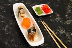 寿司和sushimi在一块白色板材在桌上反对黑暗的背景 免版税图库摄影
