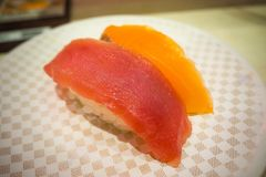 寿司在白色板材的100日元在日本餐馆在东京 免版税库存图片