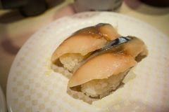 寿司在白色板材的100日元在日本餐馆在东京 库存图片