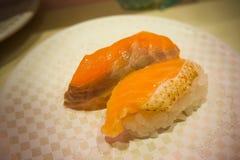 寿司在白色板材的100日元在日本餐馆在东京 库存照片