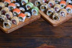 寿司套一定数量的卷在桌上的一个木切板位于寿司店的厨房 一个传统盘 免版税图库摄影