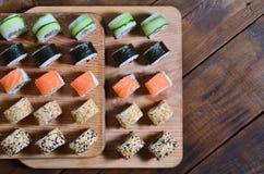 寿司套一定数量的卷在桌上的一个木切板位于寿司店的厨房 一个传统盘 免版税库存照片