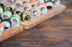 寿司套一定数量的卷在桌上的一个木切板位于寿司店的厨房 一个传统盘 免版税库存图片
