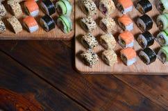 寿司套一定数量的卷在桌上的一个木切板位于寿司店的厨房 一个传统盘 图库摄影