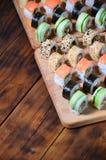寿司套一定数量的卷在桌上的一个木切板位于寿司店的厨房 一个传统盘 库存照片