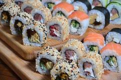 寿司套一定数量的卷在桌上的一个木切板位于寿司店的厨房 一个传统盘 库存图片