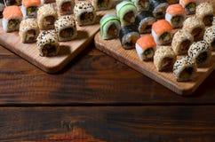 寿司套一定数量的卷在桌上的一个木切板位于寿司店的厨房 一个传统盘o 免版税图库摄影