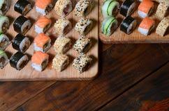 寿司套一定数量的卷在桌上的一个木切板位于寿司店的厨房 一个传统盘o 免版税库存照片