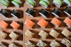 寿司套一定数量的卷在桌上的一个木切板位于寿司店的厨房 一个传统盘o 图库摄影