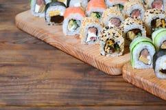 寿司套一定数量的卷在桌上的一个木切板位于寿司店的厨房 一个传统盘o 库存照片