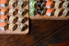 寿司套一定数量的卷在桌上的一个木切板位于寿司店的厨房 一个传统盘o 库存图片