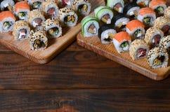 寿司套一定数量的卷在桌上的一个木切板位于寿司店的厨房 一个传统盘o 免版税库存图片