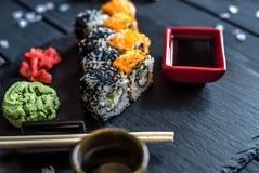 寿司用在桌上的黑和红色鱼子酱 免版税库存照片