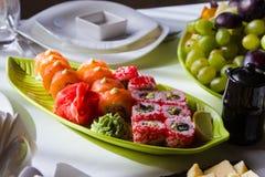 寿司膳食在绿色玻璃板材服务用柠檬,山葵并且用了卤汁泡姜,鲜美和新鲜,餐馆,食物菜单照片 免版税库存照片