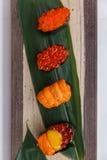 寿司集合包括Tobiko、Ikura,海胆和Ikura、野孩子和在石板材的叶子供食的鹌鹑蛋卵黄质 图库摄影