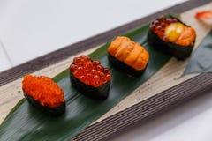 寿司集合包括Tobiko、Ikura,海胆和Ikura、野孩子和在石板材的叶子供食的鹌鹑蛋卵黄质 库存照片