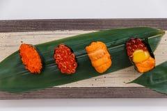 寿司集合包括Tobiko、Ikura,海胆和Ikura、野孩子和在石板材的叶子供食的鹌鹑蛋卵黄质 免版税库存照片