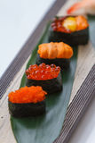 寿司集合包括Tobiko、Ikura,海胆和Ikura、野孩子和在石板材的叶子供食的鹌鹑蛋卵黄质 免版税库存图片