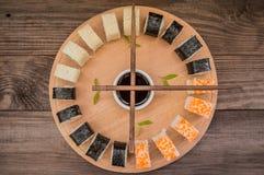 寿司集合生鱼片和卷在一个木板 背景 顶视图 免版税库存图片