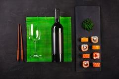 寿司集合生鱼片和寿司卷、瓶酒和在石板岩服务的玻璃 图库摄影