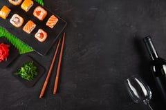 寿司集合生鱼片和寿司卷、瓶酒和在石板岩服务的玻璃 库存照片
