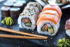 寿司集合生鱼片和寿司卷在石板岩服务 库存图片