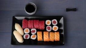 寿司集合nigiri和卷在黑色的盘子服务与筷子、酱油、山葵和姜 平的位置 影视素材