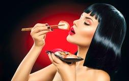 寿司 秀丽吃寿司的模型女孩画象  免版税库存图片