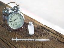 射入、瓶、药片和手表意味着射入的时刻的糖尿病患者要求胰岛素射入 免版税库存照片
