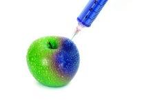 射入充满活力的蓝色到与注射器的红色新鲜的湿苹果里在白色背景为更新能量、GMO或者合成物质或者助力e 免版税库存图片