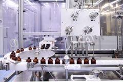 射入的不育的胶囊 在配药植物的装瓶专线的瓶 机器在检查不育的液体以后 免版税库存照片